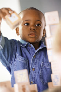 OTvest-black_boy_stacking_blocks_in_denim